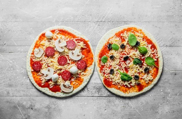 Dwa różne surowe pizze na białym drewnianym stole