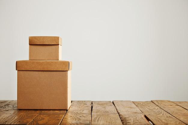 Dwa różnej wielkości beżowe pudełka z tektury falistej bez etykiet, umieszczone jeden na drugim, na białym tle