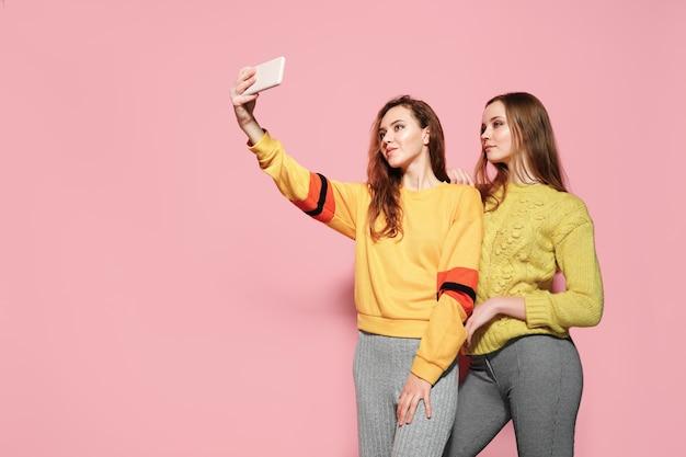 Dwa rozochoconej młodej kobiety opowiada selfie