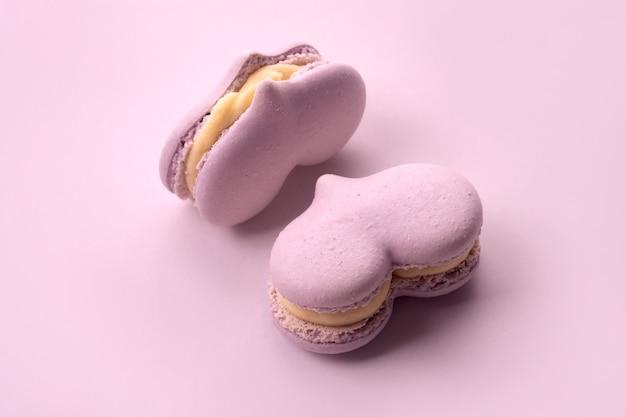Dwa różowe ciasta makaronikowe w formie serduszka, pastelowe kolory. małe słodkie ciasta.