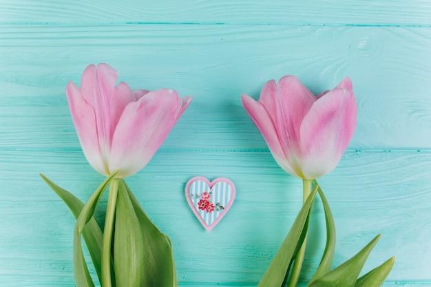 Dwa różowego tulipanu i dekoracyjnego serce na błękitnym drewnianym tle