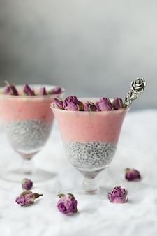 Dwa różowy deser z tapioki zwieńczony różowymi pąkami róży