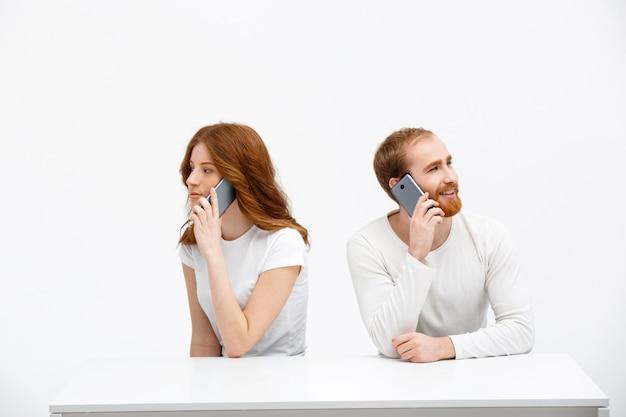 Dwa rudzielec nad stołem opowiada telefon komórkowego