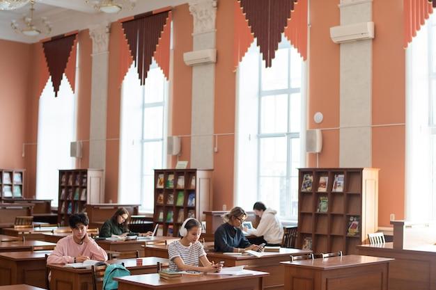 Dwa rzędy ławek w bibliotece uczelni i studenci pracujący indywidualnie przygotowując się do seminarium po zajęciach
