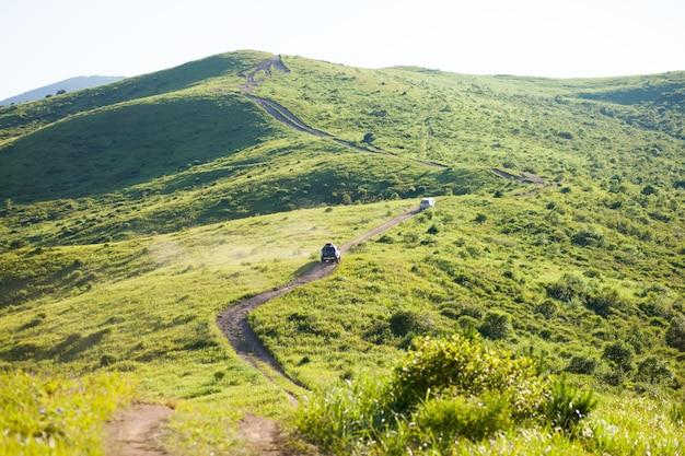 Dwa samochody 4*4 wspinają się po zielonym wzgórzu