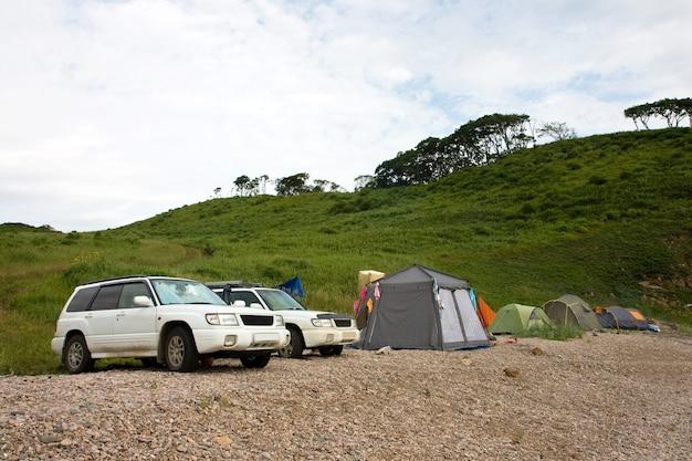 Dwa samochody i obóz nad brzegiem morza
