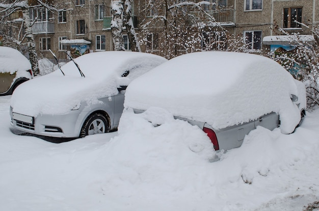 Dwa samochody w zaspach śnieżnych po śniegu w zimie nie czyszczone