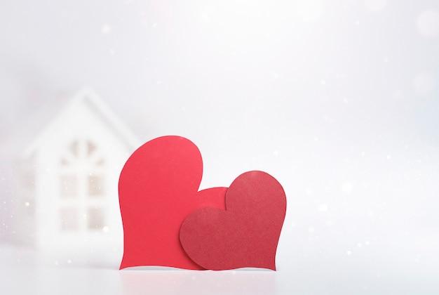 Dwa serca na pierwszym planie, domek z zabawkami w ścianie