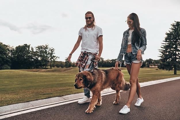 Dwa serca pełne miłości. pełna długość pięknej młodej pary spacerującej z psem podczas spędzania czasu na świeżym powietrzu