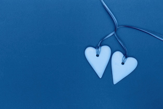 Dwa serca razem w klasycznym stonowanym kolorze niebieskim. koncepcja miłości romantycznej. t walentynki tło. minimalistyczny styl.