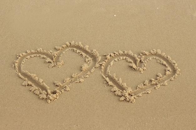 Dwa serca rysowane w piasku na plaży.