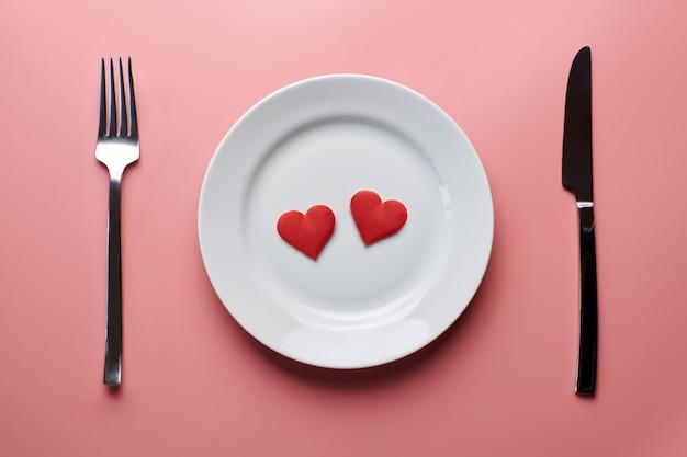 Dwa serca w talerzu ze sztućcami. romantyczna kolacja w restauracji. spotkanie kochanków na przyjęciu weselnym.
