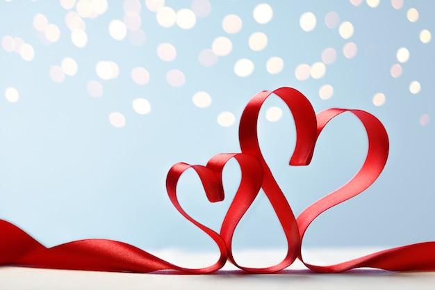 Dwa serca wykonane z czerwonych wstążek na niebieskim tle ze złotymi światłami. karta walentynki