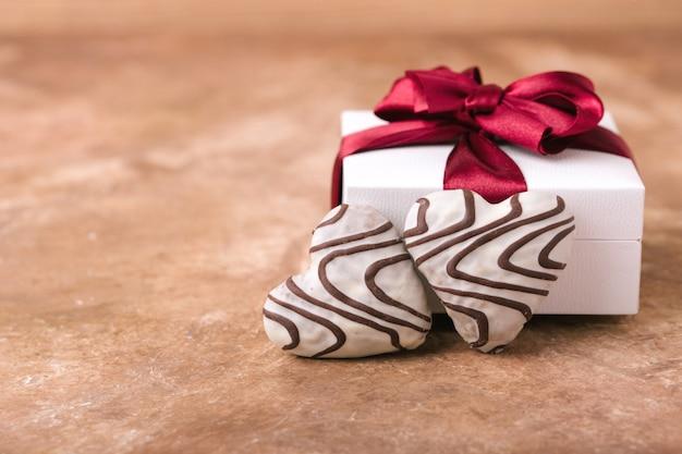 Dwa serca z piernika, w białej glazurze i liniach czekoladowych, lekkie pudełko z bordową satynową kokardką, miejsce na tekst, brązowe tło