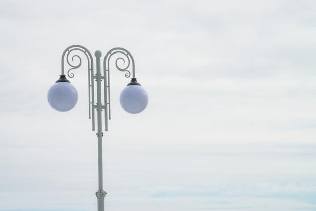 Dwa sferyczne lampy uliczne na białym rocznika filarze na lekkim nieba tle z kopii przestrzenią.