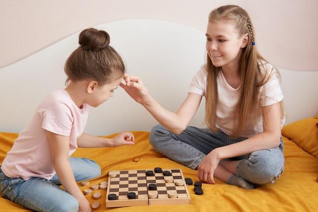 Dwa siostry bawić się warcabów na złym ma zabawę w domu, szczęśliwy dziecka pojęcie