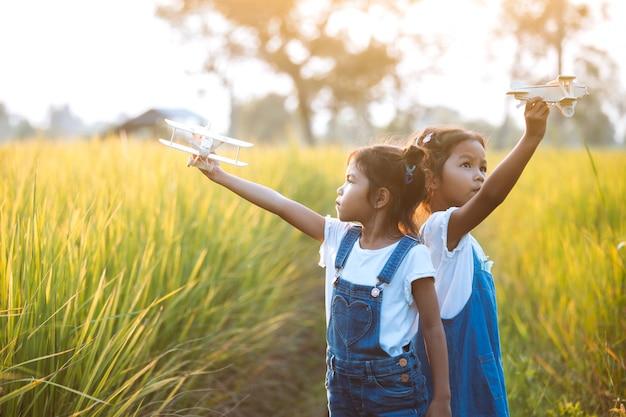 Dwa ślicznej azjatykciej dziecko dziewczyny bawić się z zabawkarskim drewnianym samolotem w polu