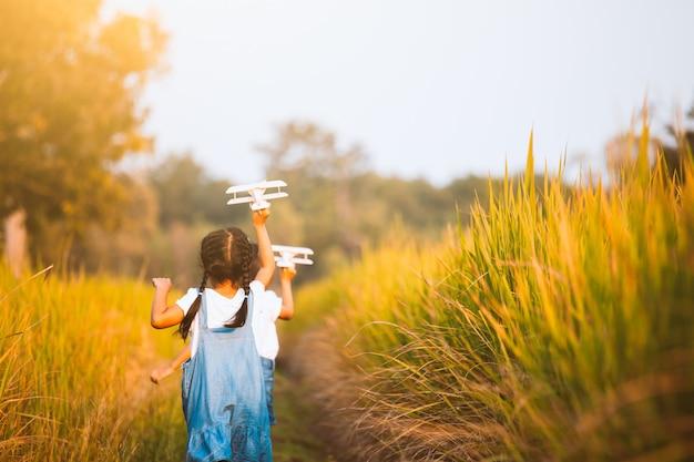 Dwa ślicznej azjatykciej dziecko dziewczyny biega i bawić się z zabawkarskim drewnianym samolotem w polu