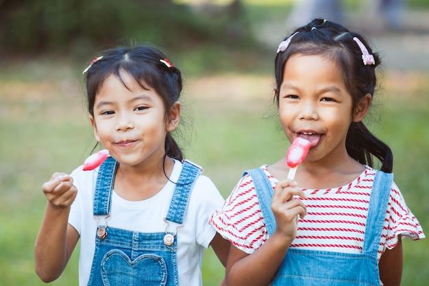 Dwa ślicznej azjatykciej dziecko dziewczyny je lody w parku wpólnie