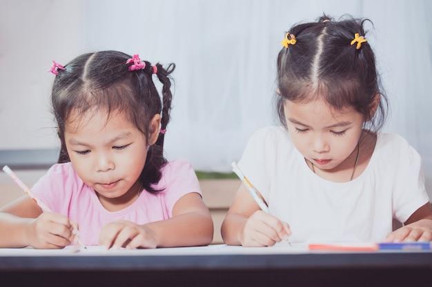 Dwa ślicznej azjatykciej dziecko dziewczyny ma zabawę rysować wpólnie i malować w rocznika koloru brzmieniu