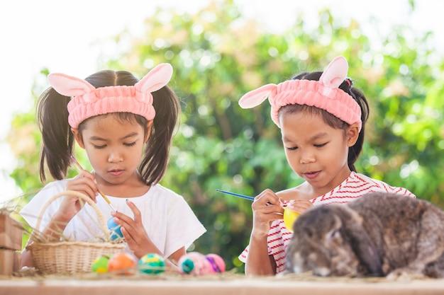 Dwa ślicznej azjatykciej dziecko dziewczyny rysuje i maluje na easter jajkach wpólnie przygotowywają dla easter dnia