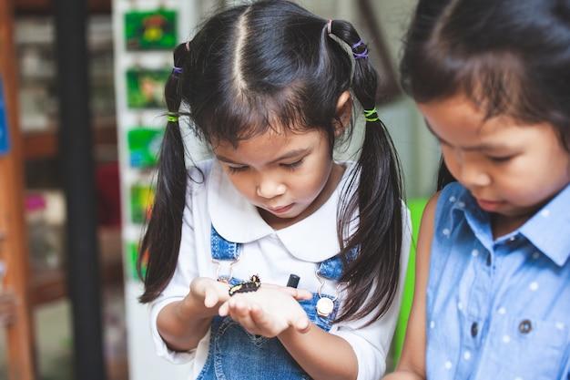 Dwa ślicznej azjatykciej dziecko dziewczyny trzyma i bawić się z czarną gąsienicą