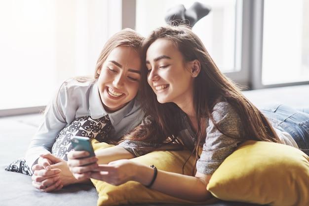 Dwa ślicznej uśmiechniętej bliźniak siostry trzyma smartphone i robi selfie. dziewczyny leżą na kanapie pozując i radując się