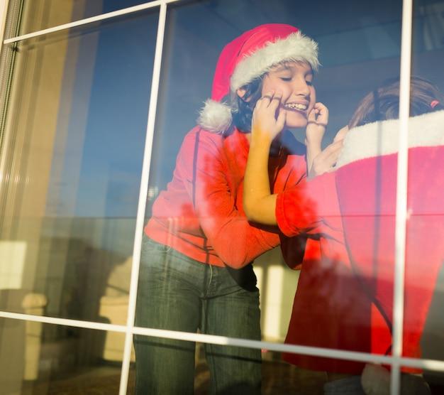 Dwa słodkie chłopców braci w oknie czeka na mikołaja i nowy rok
