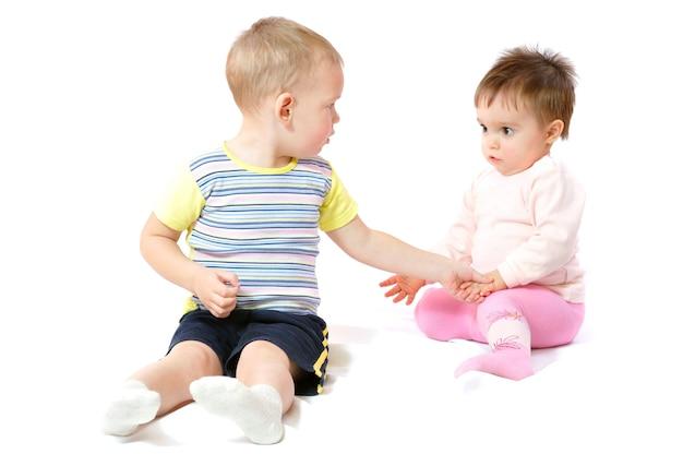 Dwa słodkie małe dzieci siedzi i gra.