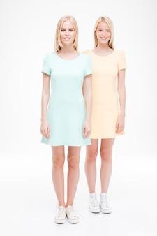 Dwa słodkie młode kobiety stojąc na białym tle nad białą ścianą