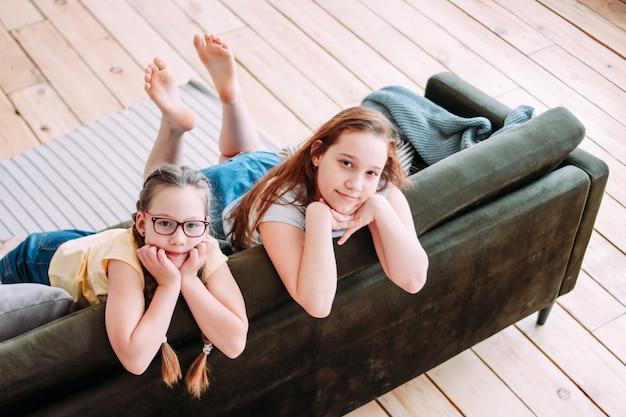 Dwa słodkie uśmiechnięte dziewczyny dzieci przyjaciół tweens siedzi na kanapie w domu