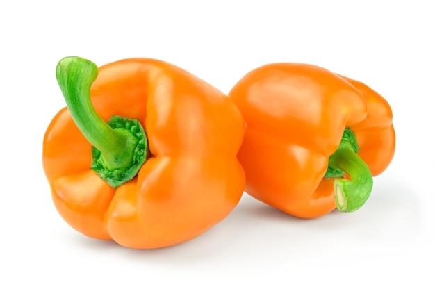 Dwa słodkiej papryki pomarańczowej na białym tle na białej powierzchni wyłącznik.