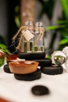Dwa słoiki aromatycznych olejków stojące na kamieniach do kamienia terapeutycznego i umieszczone na ręczniku frotte, obok których są przezroczyste kulki z bliska