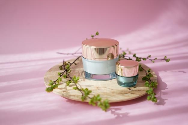 Dwa słoiki kosmetyczne na drewnianym talerzu na różowo
