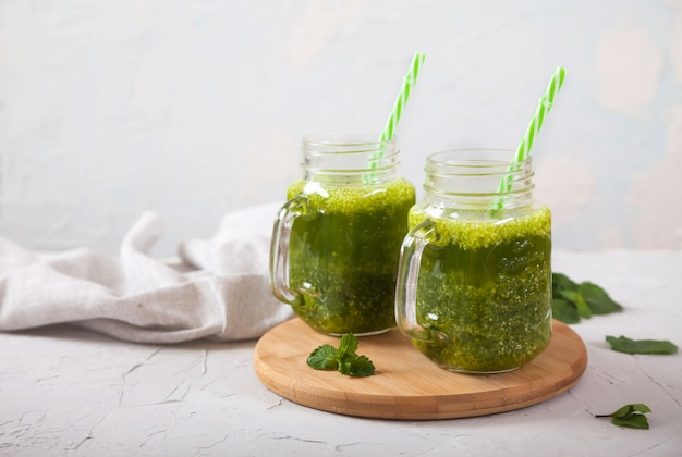 Dwa słoiki z zielonymi koktajlami na drewnianym stojaku na betonowym szarym tle. zdrowe odżywianie. detox.