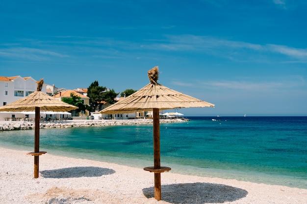 Dwa słomiane parasole na piaszczystej plaży, w pobliżu miasta primosten w chorwacji