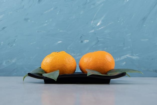 Dwa smaczne owoce klementynki na czarnym talerzu