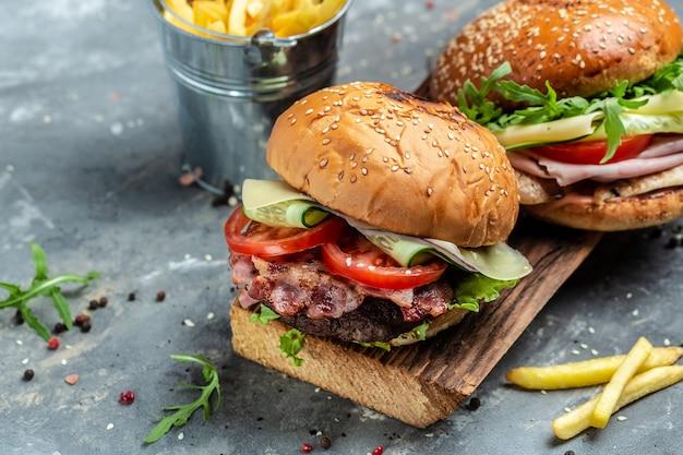 Dwa smaczne świeże burgery z bekonem, szynką i serem. amerykańskie fast foody. baner, menu, miejsce na przepis na tekst