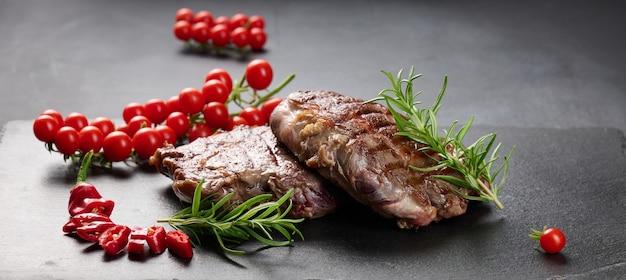 Dwa smażone kawałki wołowiny ribeye na czarnej łupkowej desce, rzadki stopień wysmażenia. apetyczny stek, baner