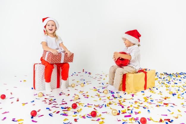 Dwa śmieszne małe dzieci w santa hat siedzi na pudełka. pojedynczo na białej ścianie, konfetti na podłodze. koncepcja bożego narodzenia i nowego roku.