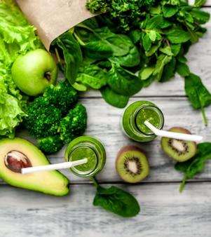 Dwa smoothie z warzywami, awokado, jabłkiem, kiwi na drewnianym tle. żywienie sportowe