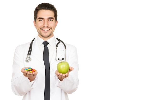 Dwa sposoby na zdrowie. połowa długości portret młodego przystojnego lekarza wyciągającego jabłko i lekarstwo, aby wybrać miejsce na boku