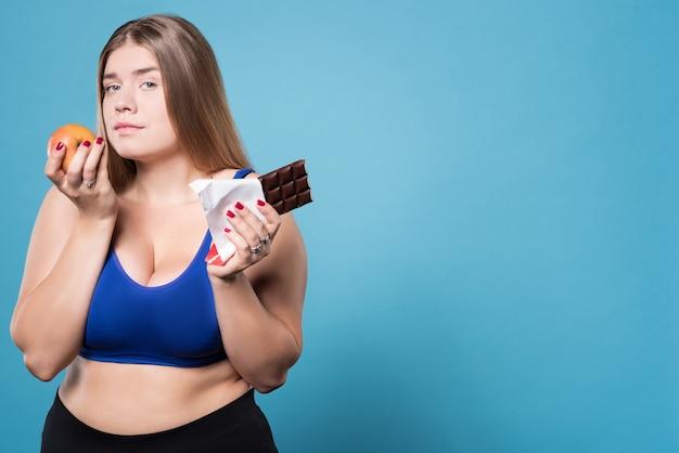 Dwa sposoby na życie. portret atrakcyjnej młodej kobiety z nadwagą stojącej z jabłkiem i czekoladą.