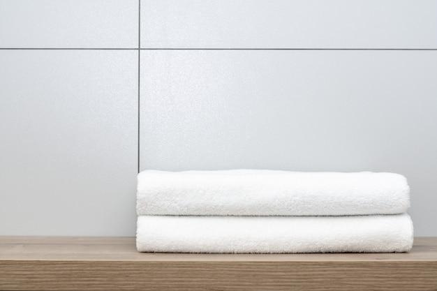 Dwa starannie złożone białe ręczniki leżą na drewnianej półce na tle płytek ceramicznych.