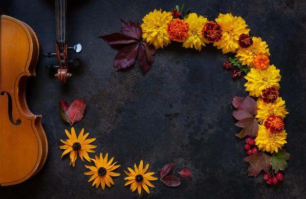 Dwa stare skrzypce i jasny wzór jesiennych kwiatów