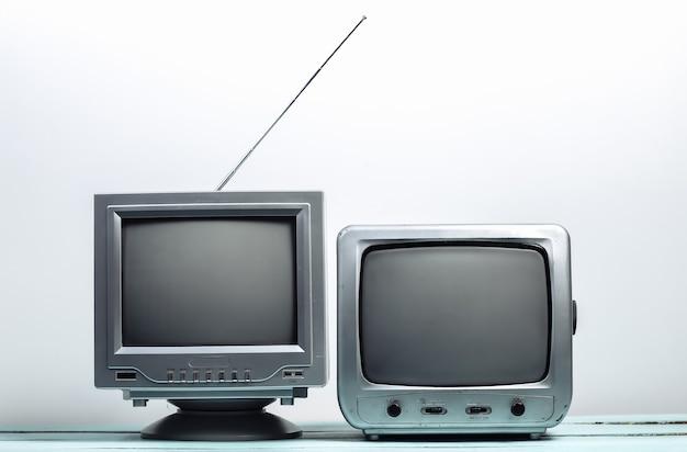 Dwa stary odbiornik telewizyjny na białej ścianie. media retro
