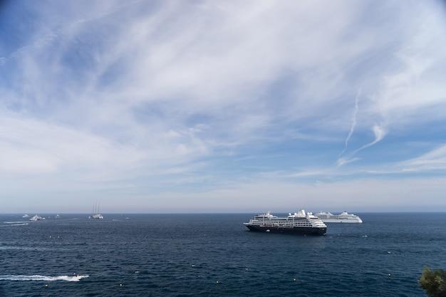 Dwa statki wycieczkowe na morzu w słoneczny dzień w otoczeniu wielu łodzi motorowych. monte carlo, monako.