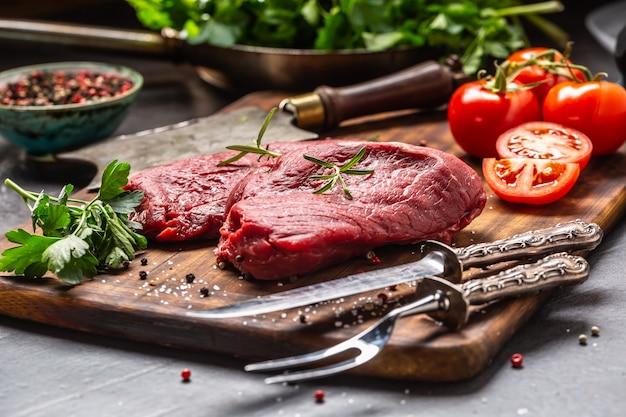 Dwa steki wołowe z ziołami, pomidorami, solą i przyprawami na desce mięsnej.