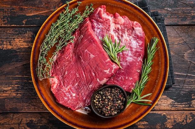 Dwa steki z surowej wołowiny flap lub flank na rustykalnym talerzu z ziołami. ciemne drewniane tło. widok z góry.