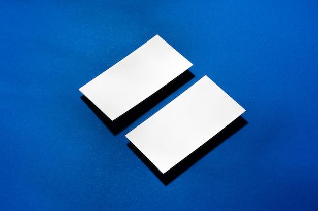 Dwa stosy pustych wizytówek na niebieskim tle z bliska